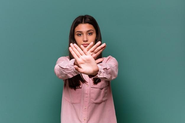 Giovane donna indiana isolata sulla parete blu che fa un gesto di diniego