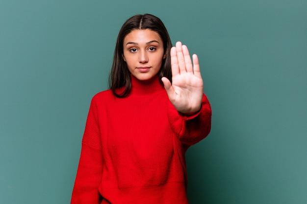 Giovane donna indiana isolata sulla parete blu in piedi con la mano tesa che mostra il segnale di stop, impedendoti.