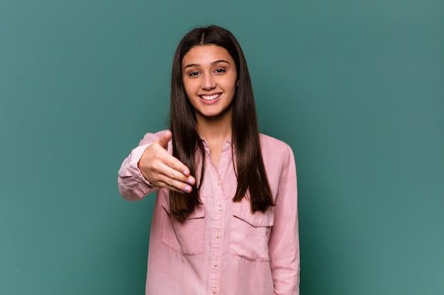 Giovane donna indiana isolata sulla parete blu che allunga la mano nel gesto di saluto.