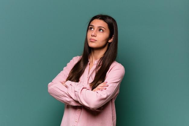 Giovane donna indiana isolata sulla parete blu stanca di un compito ripetitivo