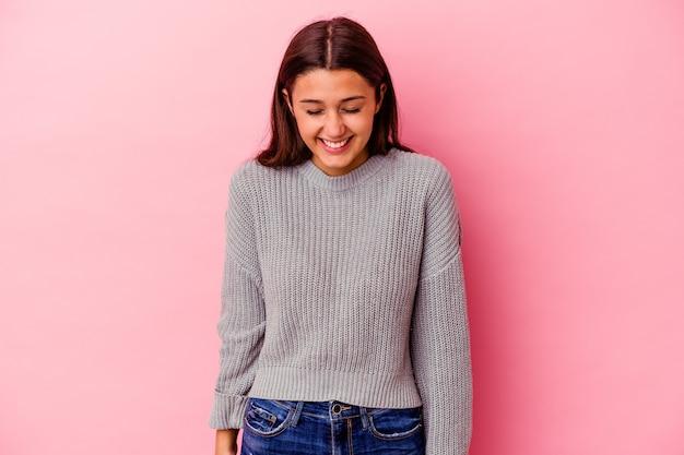 La giovane donna indiana isolata sul muro rosa ride e chiude gli occhi, si sente rilassata e felice.