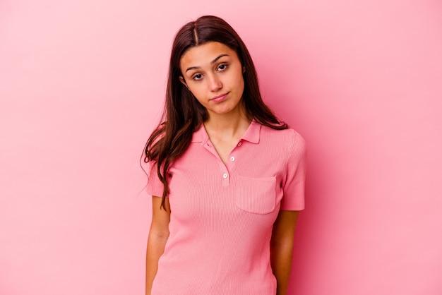 Giovane donna indiana isolata sul muro rosa, faccia triste e seria, sentendosi infelice e dispiaciuta.