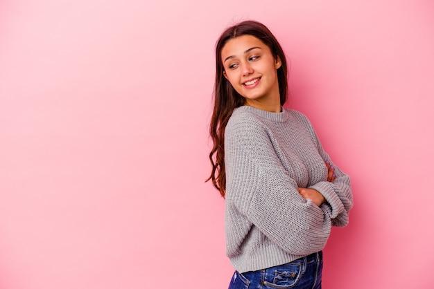 Giovane donna indiana isolata sul muro rosa sorridente fiducioso con le braccia incrociate.