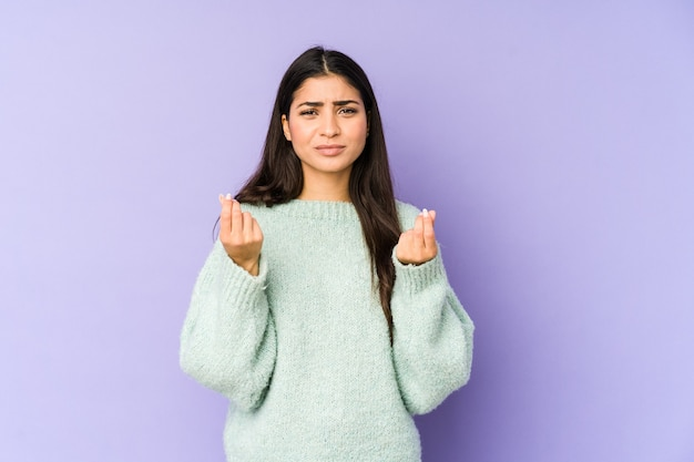 Giovane donna indiana isolata su sfondo viola, mostrando che non ha soldi.