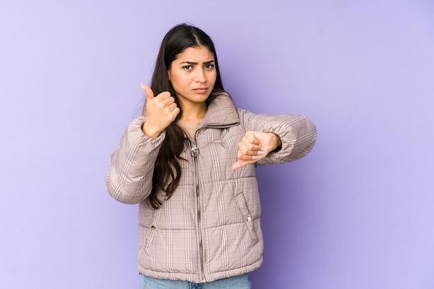 Giovane donna indiana isolata su sfondo viola che mostra i pollici in su e in giù, difficile scegliere il concetto