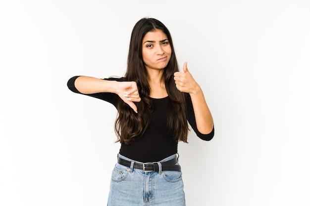 La giovane donna indiana isolata sulla porpora che mostra i pollici su e pollici giù, difficile sceglie il concetto