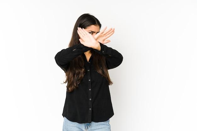 Giovane donna indiana isolata sullo spazio viola mantenendo due braccia incrociate, concetto di negazione.