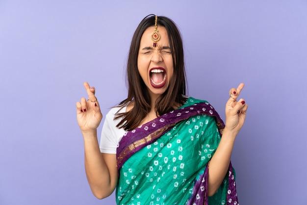 Giovane donna indiana isolata sulla parete viola con l'incrocio delle dita