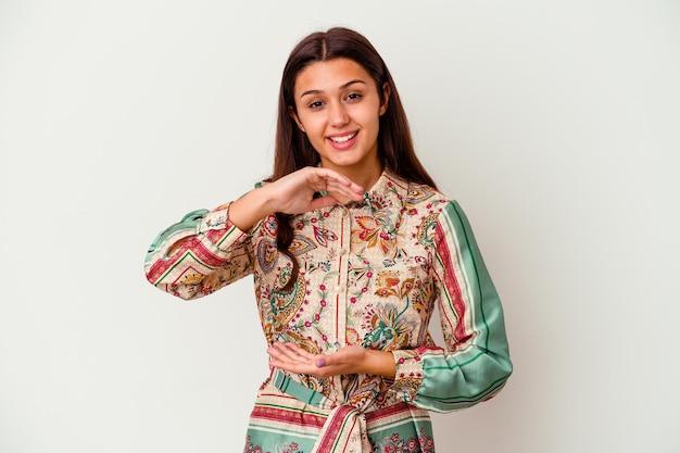 Giovane donna indiana isolata su bianco che tiene qualcosa con entrambe le mani, presentazione del prodotto.
