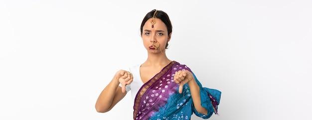 Giovane donna indiana isolata su bianco che mostra il pollice verso il basso con due mani
