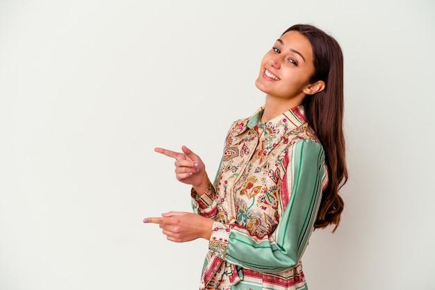 Giovane donna indiana isolata sul muro bianco eccitato che punta con gli indici di distanza.