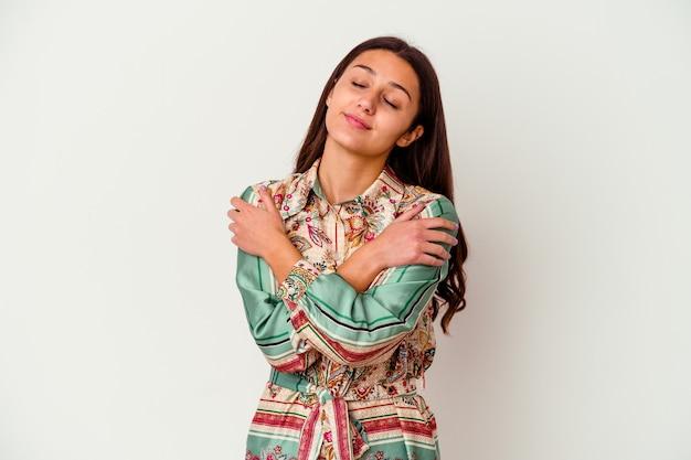 Giovane donna indiana isolata sul muro bianco abbracci, sorridendo spensierata e felice.