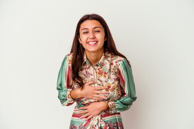 La giovane donna indiana isolata sul muro bianco ride allegramente e si diverte a tenere le mani sullo stomaco.