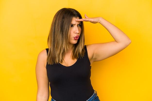 Giovane donna indiana isolata sul giallo che guarda lontano tenendo la mano sulla fronte.