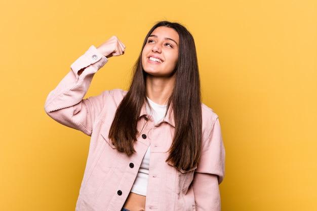 Giovane donna indiana isolata sulla parete gialla che celebra una vittoria, passione ed entusiasmo, felice espressione.