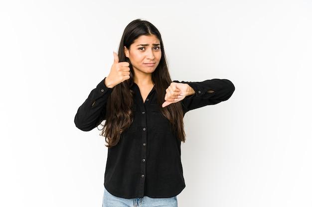 Giovane donna indiana su viola che mostra i pollici in su e in giù, difficile scegliere il concetto