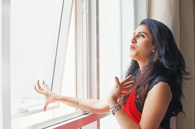 Giovane donna indiana in sari che apre la finestra a causa del caldo estivo estremo