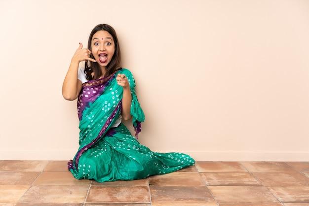 Giovane donna indiana che si siede sul pavimento che fa il gesto del telefono e che indica davanti