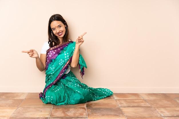 Giovane donna indiana seduta sul pavimento che punta il dito ai laterali e felice