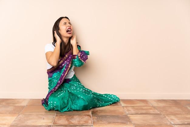 La giovane donna indiana che si siede sul pavimento ha sottolineato sopraffatta
