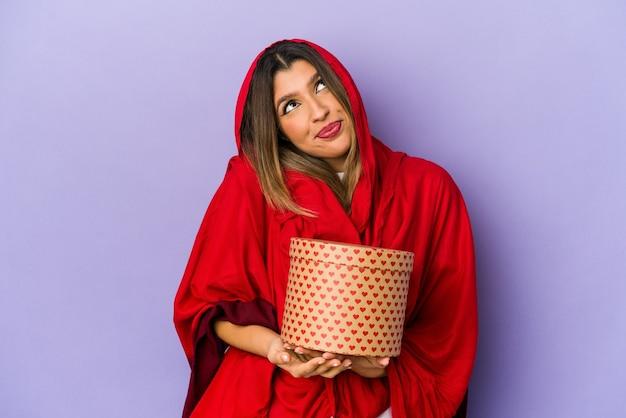 Giovane donna indiana che indossa un hijab che tiene un regalo di san valentino isolato sognando di raggiungere obiettivi e scopi