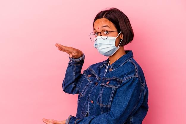 Giovane donna indiana che indossa una maschera antivirus isolata su sfondo rosa scioccata e stupita tenendo una copia spazio tra le mani.