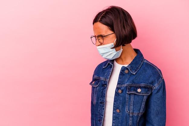 Giovane donna indiana che indossa una maschera antivirus isolata sulla parete rosa che grida verso uno spazio di copia