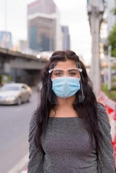 Giovane donna indiana che indossa la maschera e la protezione per il viso nelle strade della città