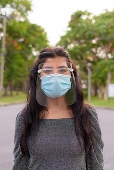 Giovane donna indiana che indossa la maschera e la protezione per il viso presso il parco all'aperto
