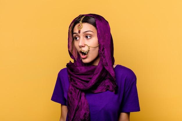 Giovane donna indiana che indossa un tradizionale sari vestiti isolati su sfondo giallo che è scioccata a causa di qualcosa che ha visto.