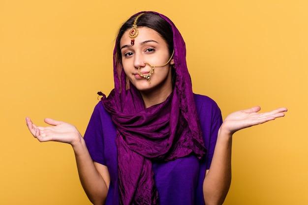 Giovane donna indiana che indossa un tradizionale sari vestiti isolati sul muro giallo dubitando e scrollando le spalle nel gesto interrogativo