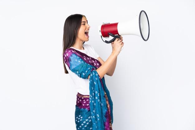 Giovane donna indiana sulla parete bianca che grida tramite un megafono