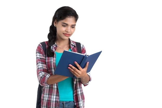 Giovane donna indiana con zaino in piedi e tenendo i notebook, in posa su un muro bianco.