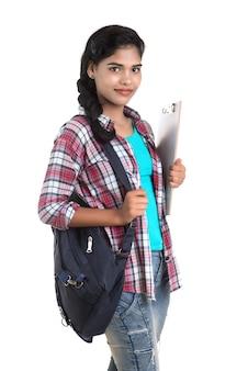 Giovane donna indiana con zaino in piedi e tenendo il bordo bianco, in posa su un muro bianco.