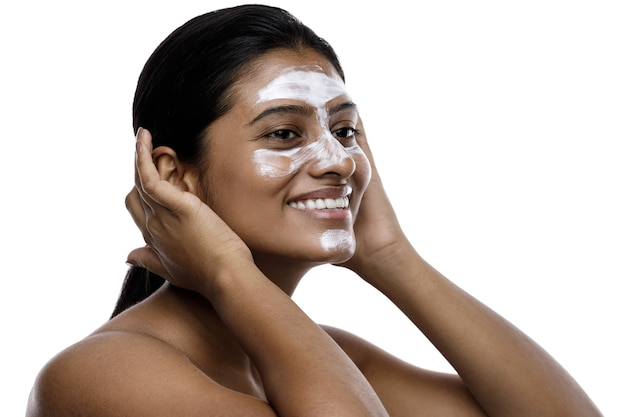 Giovane donna indiana con una maschera detergente applicata sul viso. isolato su bianco.