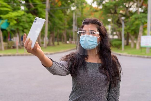 Giovane donna indiana con maschera e schermo facciale prendendo selfie al parco all'aperto