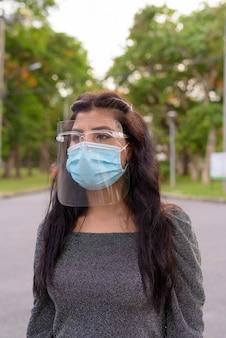 Giovane donna indiana con maschera e visiera pensando al parco all'aperto