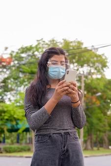 Giovane donna indiana con maschera e visiera utilizzando il telefono presso il parco all'aperto