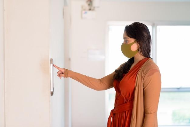 Giovane donna indiana con la maschera che preme il bottone dell'elevatore a costruzione moderna