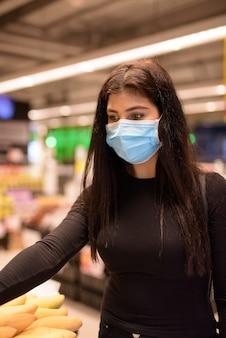 Giovane donna indiana con la maschera che fa acquisti con la distanza al supermercato