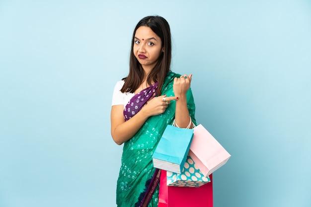 Giovane donna indiana con le borse della spesa che fa il gesto di essere in ritardo