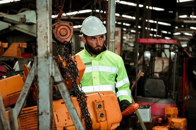 Uomo giovane operaio industriale che lavora con la macchina in metallo in fabbrica con molte attrezzature