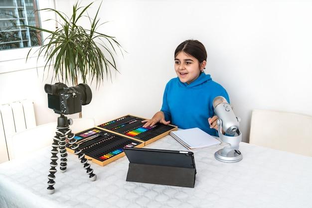 Giovane influencer e blogger che trasmette in streaming una lezione di pittura a pastelli dal suo salotto ridendo e guardando nella telecamera e parlando al microfono su una piattaforma video o di social media