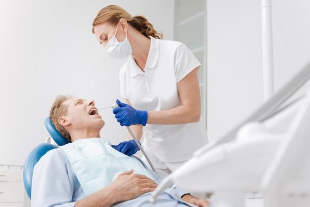 Giovane dentista innovativo capace che impiega attrezzature moderne nel suo studio mentre lavora per migliorare la salute dentale dei pazienti