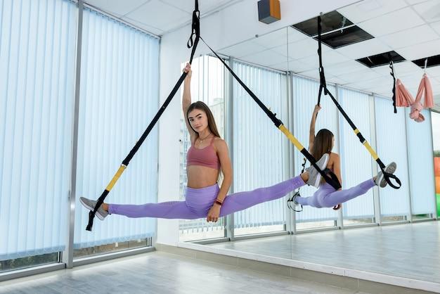 Giovane istruttore che fa esercizio di fitness con trx in studio. allenamento attivo dell'atleta femminile