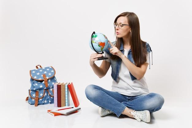 Giovane studentessa intelligente interessata che tiene il dito sul globo mondiale imparando a conoscere i paesi seduti vicino al libro di scuola dello zaino
