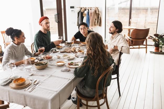 Giovani amici internazionali seduti a tavola pieni di cibo che parlano sognante tra loro