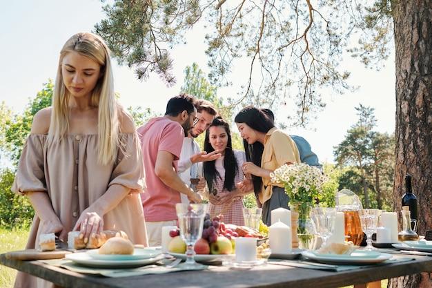 Giovani amici internazionali che parlano in ambiente naturale da tavola servita sotto un albero di pino mentre ragazza bionda che taglia il pane fresco per la cena