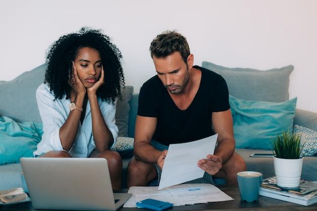 Le giovani coppie interrazziali nel divano hanno sottolineato problemi finanziari facendo calcoli con il lavoro di ufficio