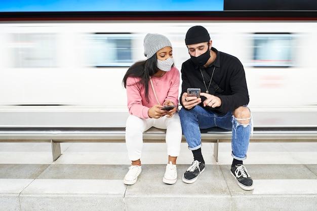 Una giovane coppia interrazziale di amanti con maschere e cappelli di lana siede in metropolitana